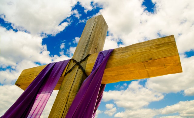Cross with purple drape or sash for Easter with blue sky and clo