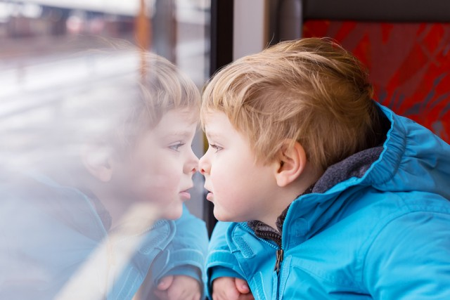 Cute Child Traveling And Looking Out Train Window Outside
