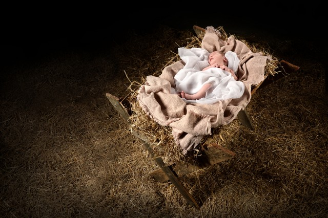 New born Jesus laying on a manger over dark background