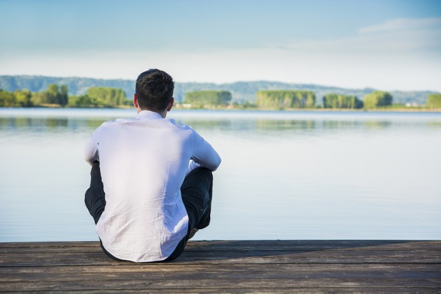 Handsome young man on a lake in a sunny, peaceful day, sitting on a wood pier, thinking or meditating