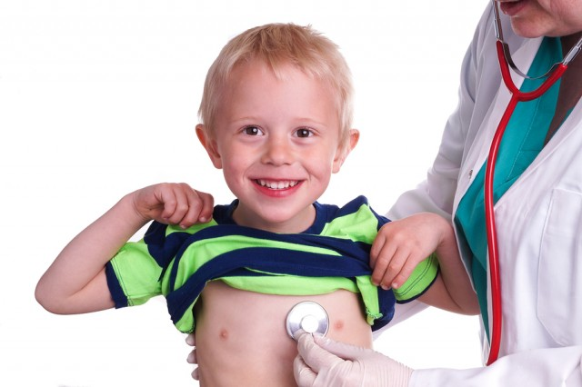 Doctor examines a young child. The doctor examines the child and listening to the heart and lungs with her stethoscope. He helps doctor by lift his shirt up so the nurse can come to listen to the boy's chest