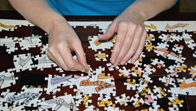 women's hands working on jigsaw puzzle pasing time away as a hobby