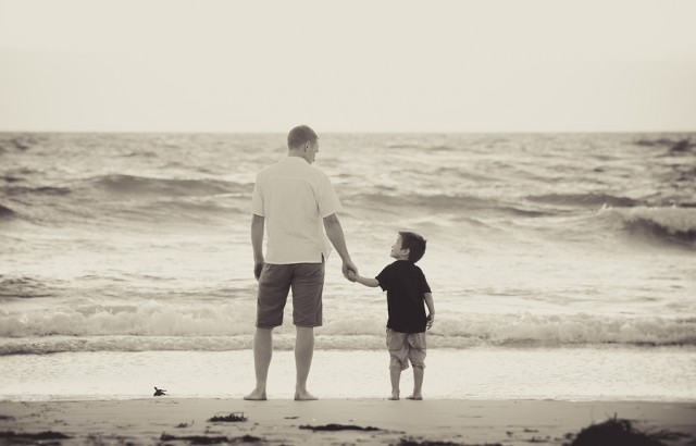 young happy father holding hand of little son walking together on the beach with barefoot in sand in front of sea waves the kid smiling and having fun with dad in Summer sunset coast