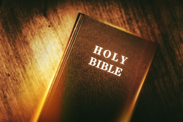 Holy Bible in Dark Browny Vintage Color Grading. Glowing Light Holy Bible