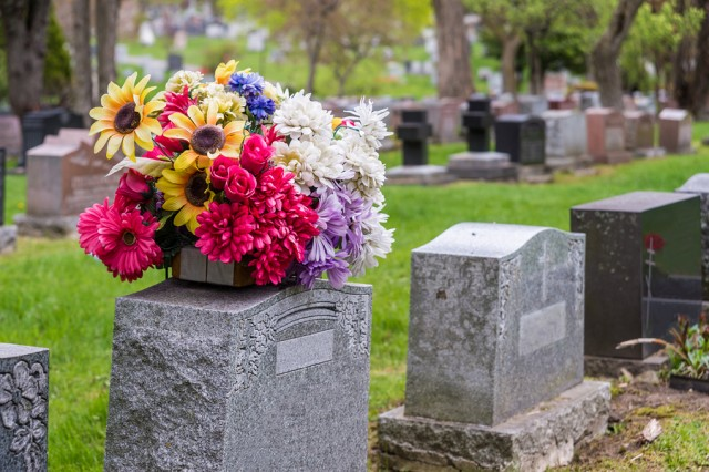 Flowers on a tombstone in a cemetery with headstones in the background