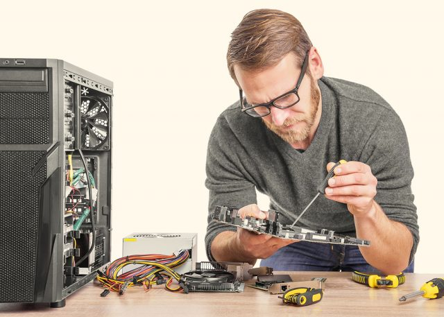 Computer repair. Computer technician working on a personal computer.