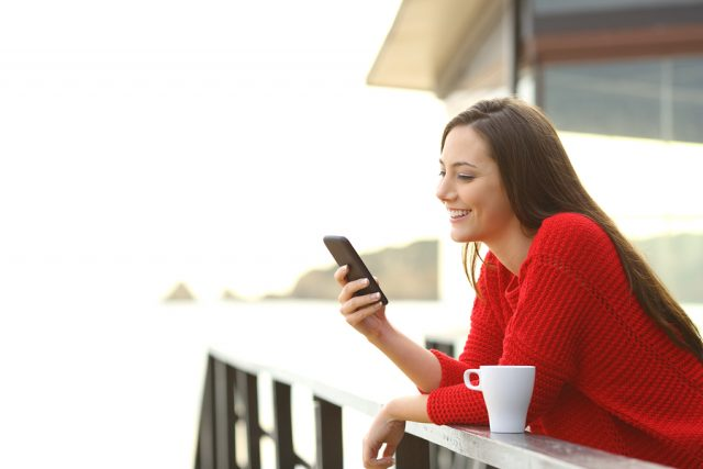 Side view portrait of a happy casual woman wearing a red sweater using a mobile phone in a balcony of a house in the beach