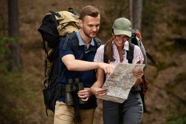 Hiking couple. Young people makes a hike in the woods. Active lifestyle, tourism. Tourist equipment.