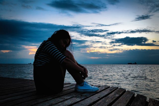 Beautiful woman in frustrated depression sitting on wooden bridge near the beach on sunset. Concept of unemployed sadness depressed and human problems in dark tone.