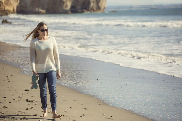 Woman walking alone along a peaceful beach thinking and pondering