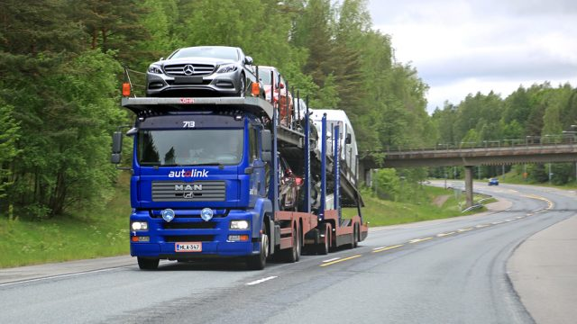 RAASEPORI, FINLAND - MAY 31, 2014: MAN car carrier hauls a full load of new cars. The Finnish automotive industry estimates that a total of 109000 new passenger cars will be sold in Finland in 2015.