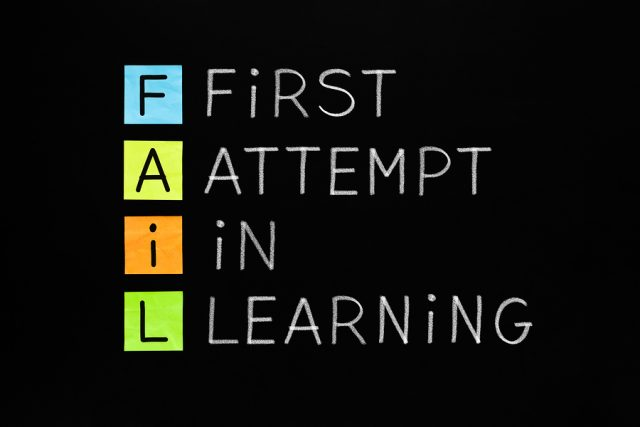 FAIL acronym First Attempt In Learning handwritten with white chalk on blackboard.