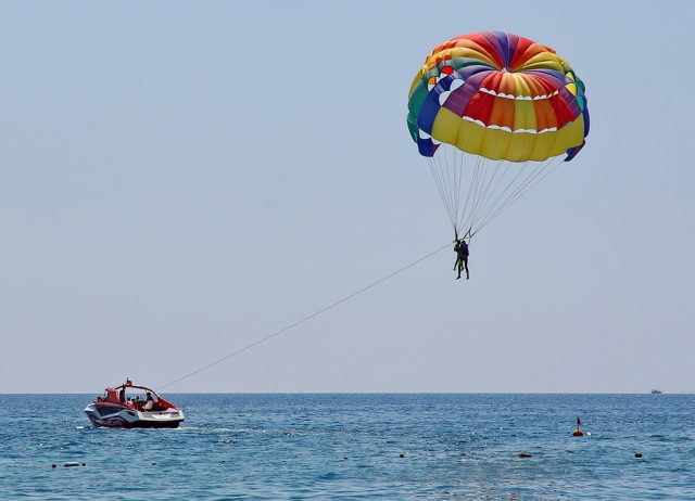 KEMER TURKEY - AUGUST 18 2015: Parasailing in a blue sky near sea beach. Parasailing is a popular recreational activity among tourists in Turkey.